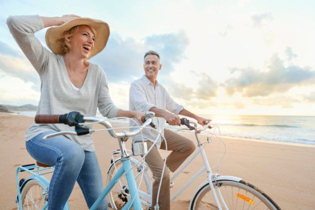Mature couple cycling on the beach at sunset or sunrise. They are laughing and having fun. They are casually...