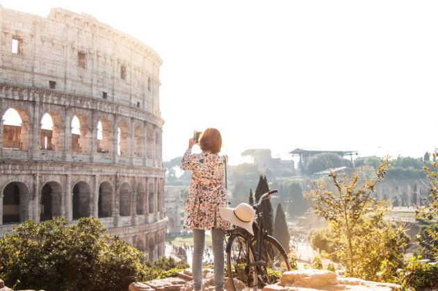 Beautiful young woman in colorful fashion dress alone on a hill with bike takes pictures of colosseum...
