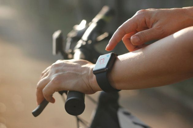 Woman cyclist hands with heart rate icon on smart watch, bicycle at summer trail. All on screen are design...