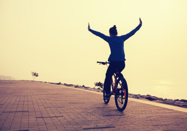 cyclist riding bike with arms outstretched in the coasts