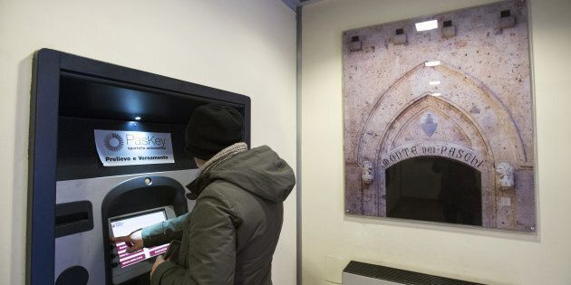 A customer uses a Bancomat automated teller machine (ATM) inside a Banca Monte dei Paschi di Siena SpA...