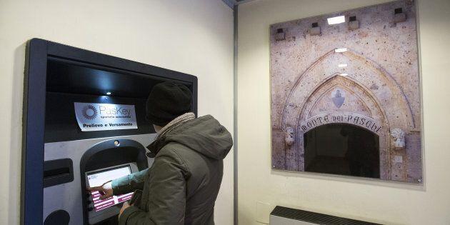A customer uses a Bancomat automated teller machine (ATM) inside a Banca Monte dei Paschi di Siena SpA...