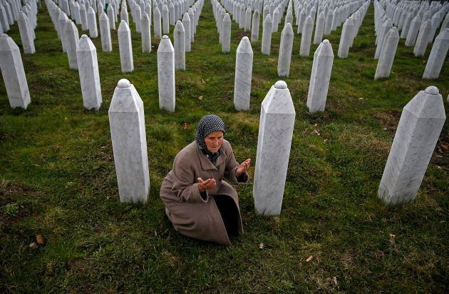Bida Smajlovic, prays at the Memorial center near the graves of her husband and brother before watching...