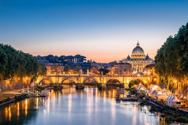view of Tiber River and Ponte Sant Angelo Bridge Saint Peter's Basilica (Vaticane) at sunset time, Rome,
