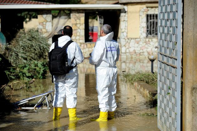 Forensic personnel check the house where according to local media nine people died in, due to the flooding...