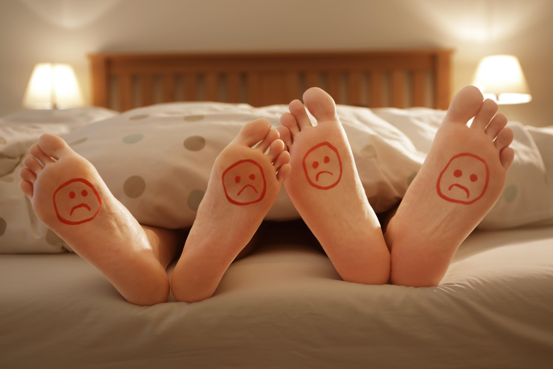 ベッドにいる男女の足に「悲しい顔」 イメージ写真