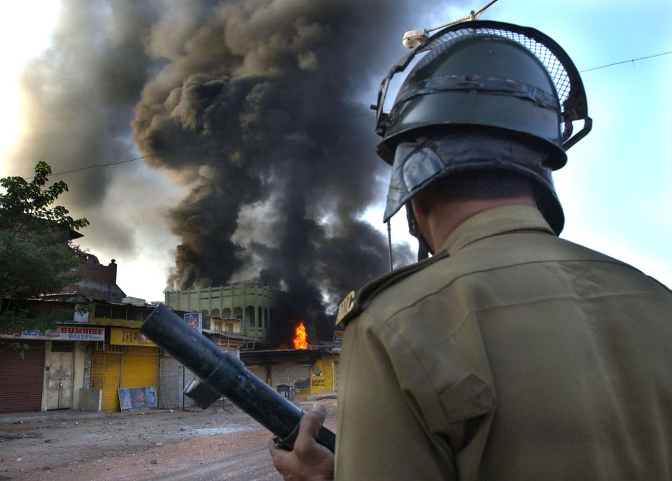 A police officer watches a Muslim-owned shop burning on March 1, 2002 in