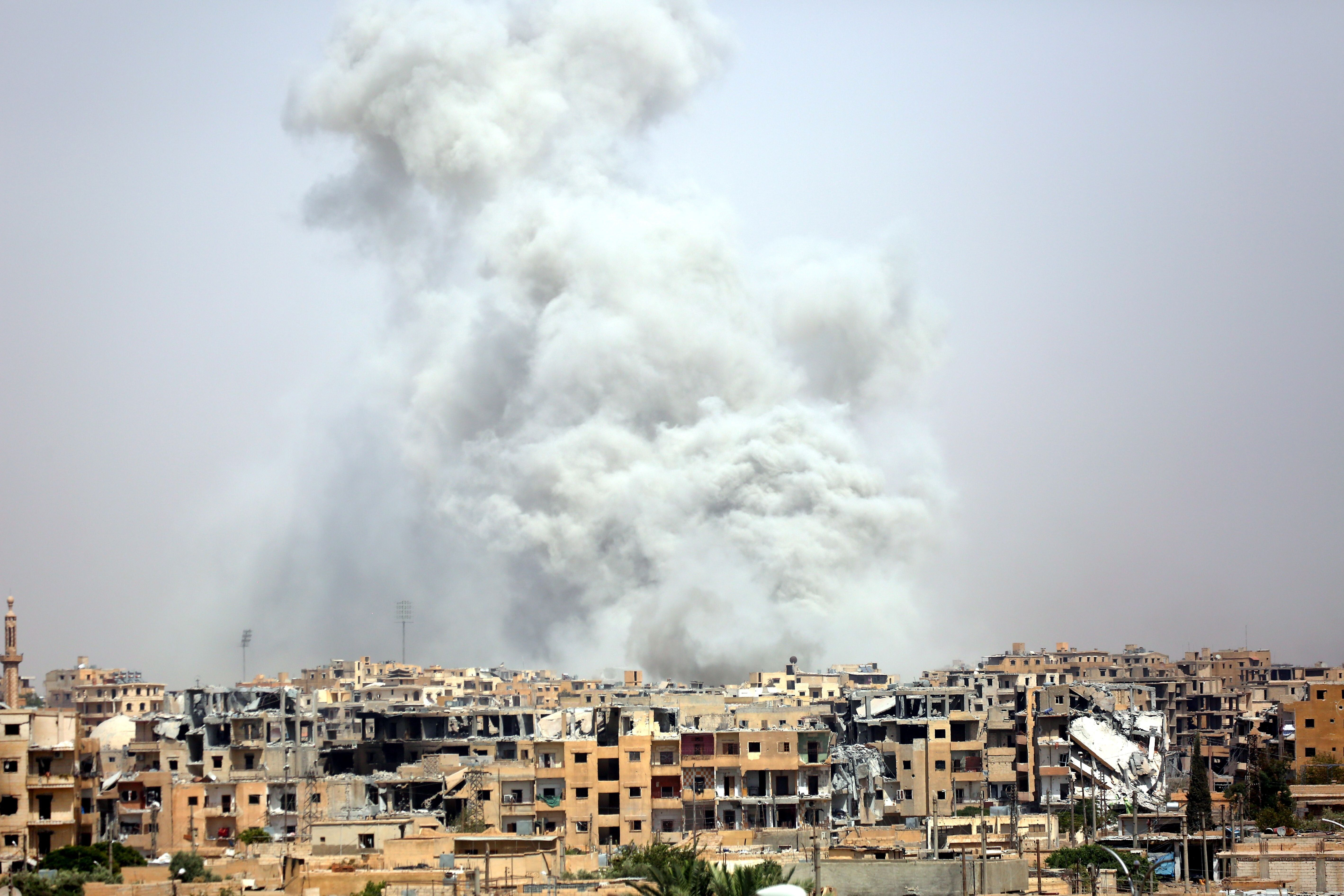 """TOPSHOT - Smoke billows out from Raqa following a coalition air strike on July 28, 2017. The Syrian Democratic Forces, a US-backed Kurdish-Arab alliance, has ousted Islamic State (IS) group jihadists from half of their Syrian bastion Raqa, where the SDF have been fighting for several months to capture the northern city which has become infamous as the Syrian heart of IS's so-called """"caliphate."""" / AFP PHOTO / DELIL SOULEIMAN        (Photo credit should read DELIL SOULEIMAN/AFP/Getty Images)"""
