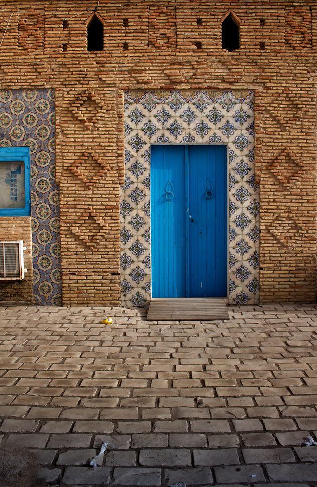 Rue avec beaucoup de détails traditionnels: vieille porte bleue avec heurtoirs, bordée...