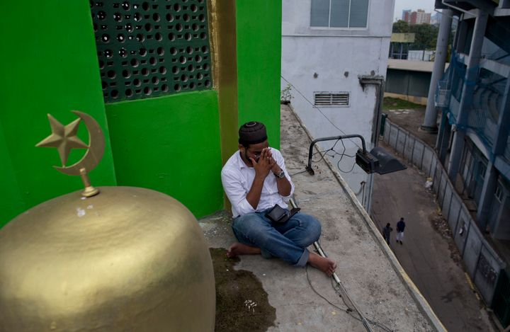 A Muslim volunteer prays perched on the roof of a mosque to spot possible hostile people during Friday prayers in Colombo, Sr