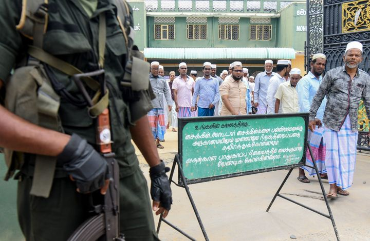 Sri Lankan security personnel stand guard outside Mohideen Meththai Grand Jumma Mosque during the Friday noon prayer in Katta