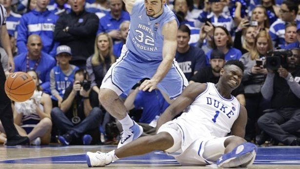 Duke basketball star Zion Williamson crashes to the floor with his Nike shoe shredded while North Carolina's Luke May chases