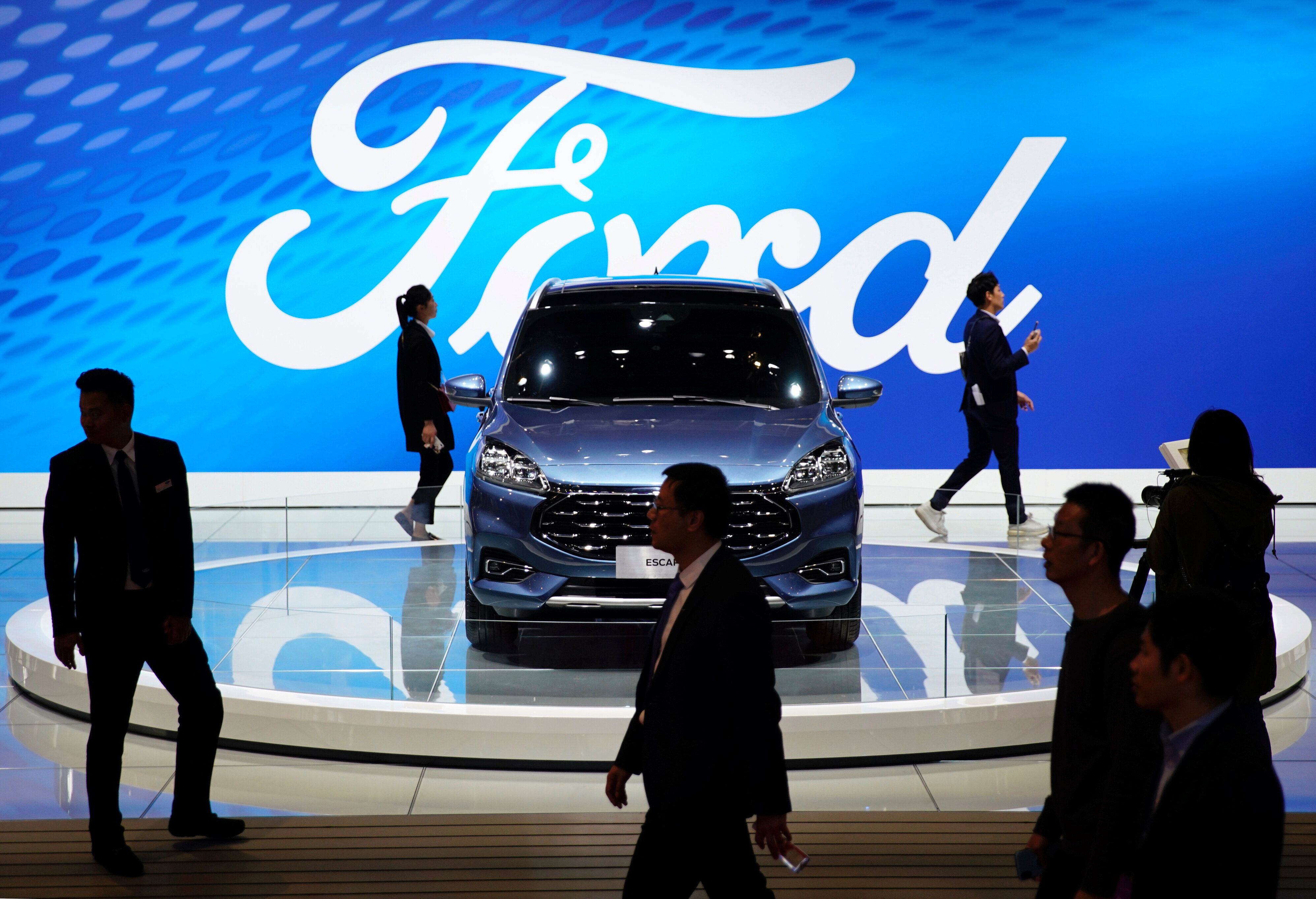 People walk by a Ford Escape SUV displayed during the media day for the Shanghai auto show in Shanghai, China April 16, 2019. REUTERS/Aly Song