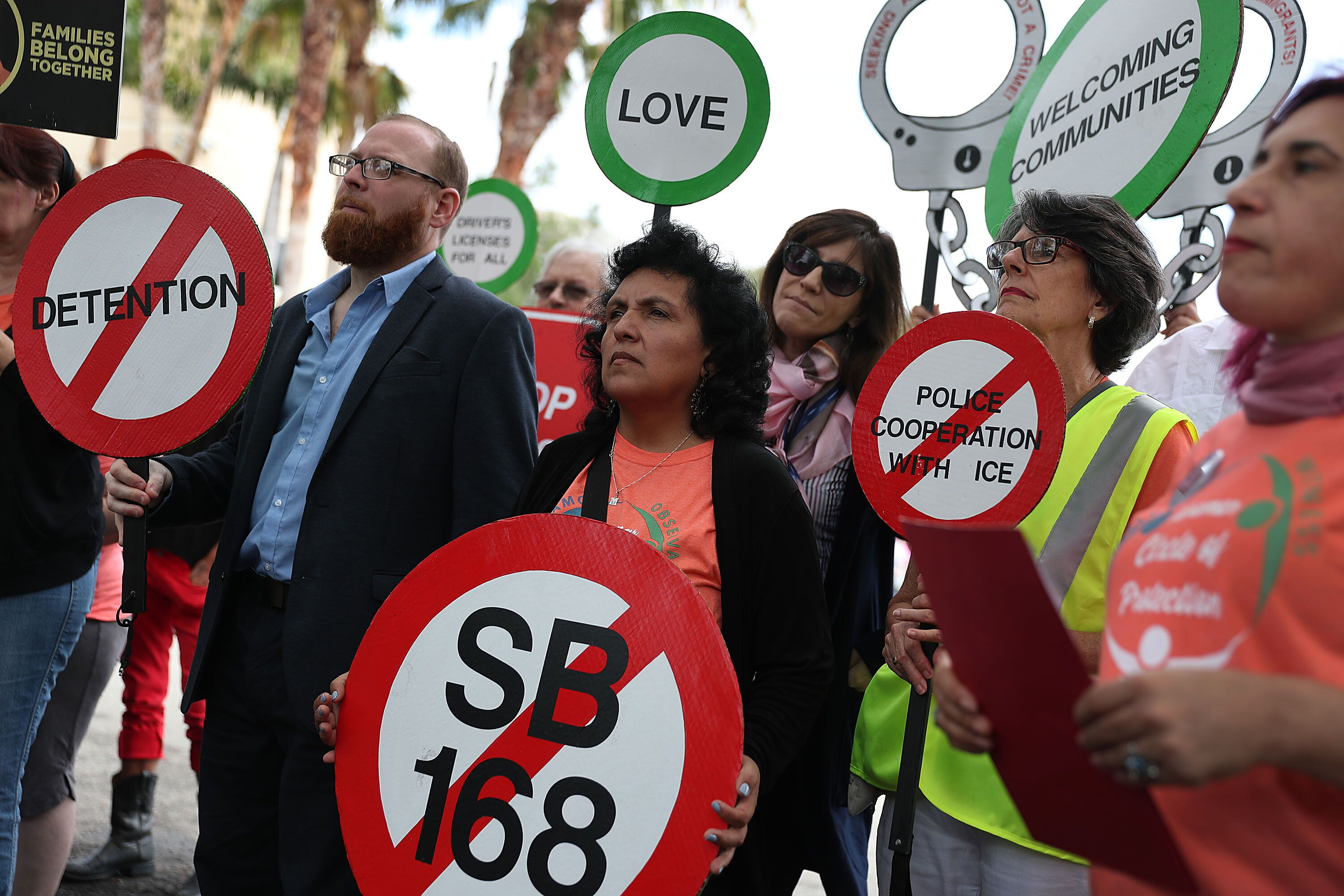 "MIRAMAR, FLORIDA - APRIL 10:  Yaquelin Lopez (C) stands with other activist during a press conference being held across the street from a U.S. Immigration and Customs Enforcement (ICE) office to announce a travel alert for the state of Florida on April 10, 2019 in Miramar, Florida. The travel alert launched this week is in response to two ""anti-sanctuary"" bills (SB 168 and HB 527) currently moving through the Florida state Legislature. The alert is meant to inform people visiting Florida of the possible increased likelihood of racial profiling, unjust detention, and possible deportation if the bills were to be enacted. (Photo by Joe Raedle/Getty Images)"