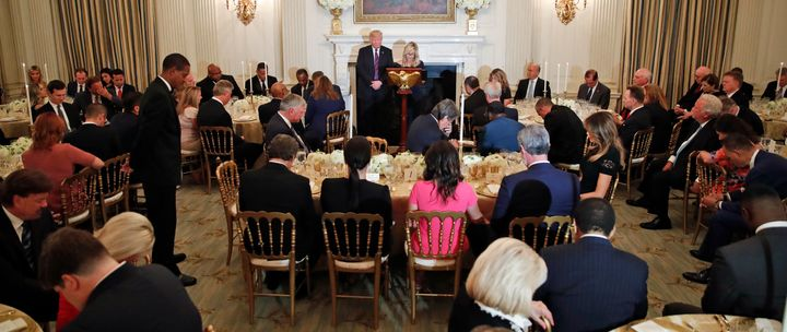 President Donald Trump bows his head as his spiritual adviser Paula White prays during an Aug. 27, 2018, dinner for evangelic