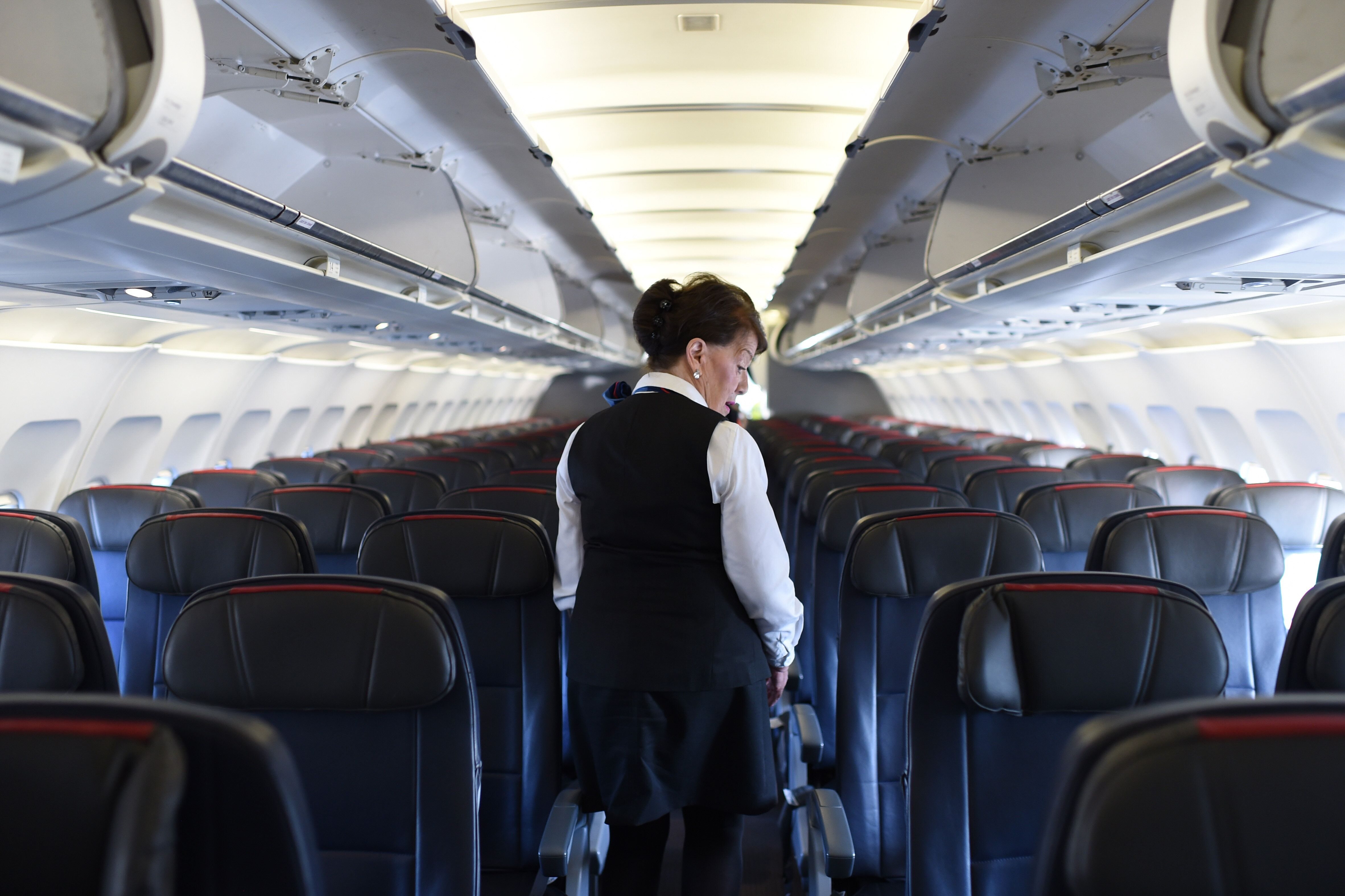 American Airlines longest serving flight attendant, Bette Nash (R), 81 years old, checks the passengers' seats for forgotten items before disembarking from her daily return flight to Boston at Ronald Reagan Washington Airport in Arlington, Virginia on December 19, 2017.   American Airlines Flight 2160 from Boston has just arrived in Washington, D.C., and Bette Nash, 81, helps the passengers disembark. After six decades crossing the skies as a flight attendant, Nash still has impeccable style, incredible energy and a constant smile. In the United States, pilots must retired at 65 but there is no such restriction on commercial flight attendants, of which Bette Nash is probably the world's most senior. / AFP PHOTO / Eric BARADAT        (Photo credit should read ERIC BARADAT/AFP/Getty Images)