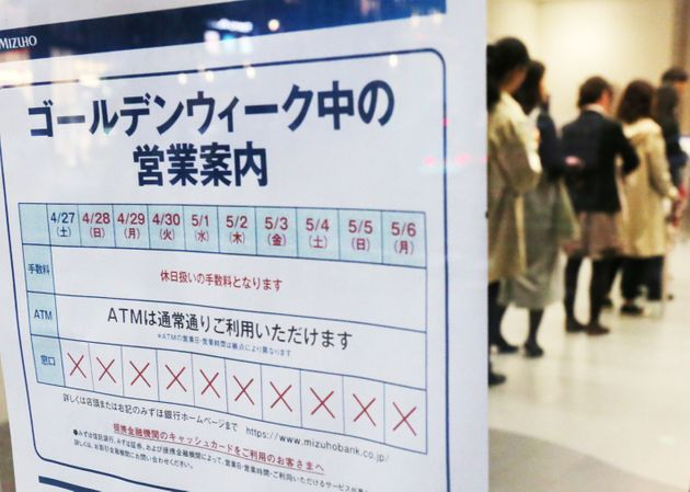 みずほ銀行の店舗に張り出された10連休中の営業案内と、現金自動預払機(ATM)に並ぶ人たち=4月26日、東京都中央区