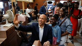 Democratic presidential candidate Sen. Cory Booker, center, takes a selfie with people at a barber shop during a campaign stop, Saturday, April 20, 2019, in Las Vegas. (AP Photo/John Locher)