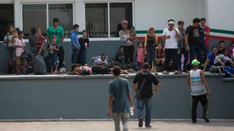 Migrants languish at an immigration detention center in Tapachula, Chiapas State, Mexico, Friday, April 26, 2019. At least 1,300 mainly Cuban migrants fled on foot from an immigration detention center on Mexico's southern border Thursday in the largest mass escape in recent memory. (AP Photo/Moises Castillo)
