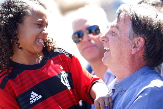 Jair Bolsonaro brinca com a menina Yasmin Alves, de 8 anos, em visita à sua casa na Estrutural,...