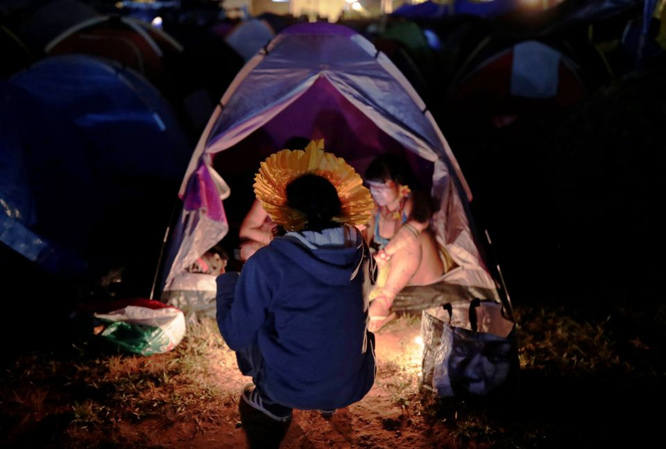 Mulheres indígenas ao lado de cabanas no Acampamento Terra