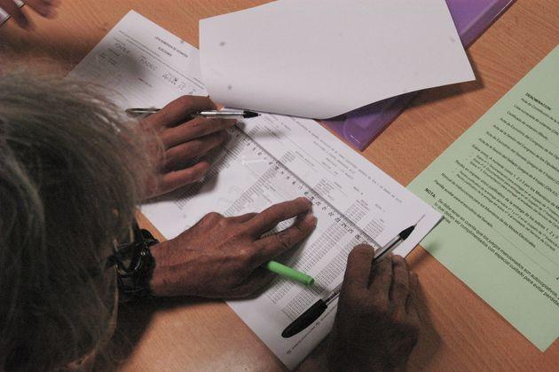 Los vocales de una mesa revisan los datos de los electores, en el colegio de Pinar del Rey, en