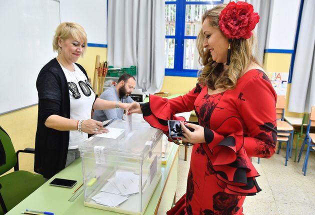 Una joven vestida de gitana vota en El Ejido, Almería, que está de