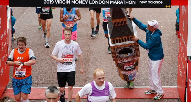 Lukas Bates wearing a costume of the Queen Elizabeth Tower - known as Big Ben - is helped by an official...