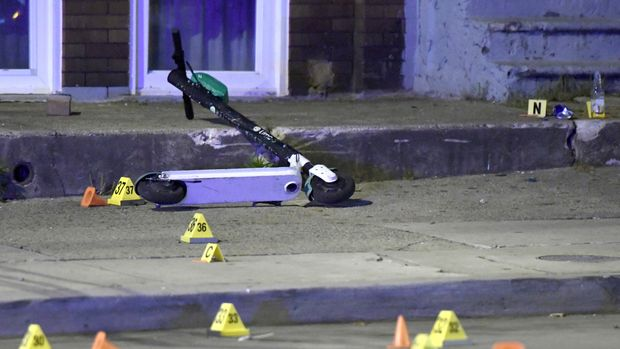 A scooter lies among evidence markers near the scene where authorities say seven people were shot, at least one fatally, Sunday, April 28, 2019, in Baltimore. (AP Photo/Steve Ruark)