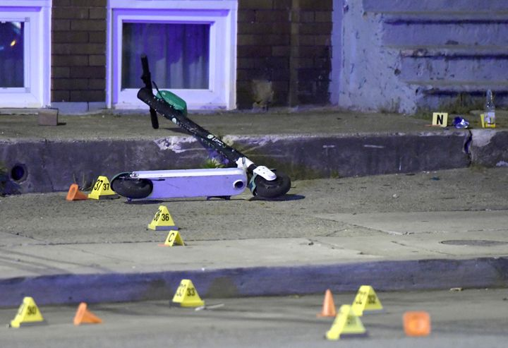 A scooter lies among evidence markers near the scene where authorities say eight people were shot, at least one fatally  Gunman Opens Fire On Cookouts In Baltimore, Killing 1 5cc65e0a2300009400d1549b