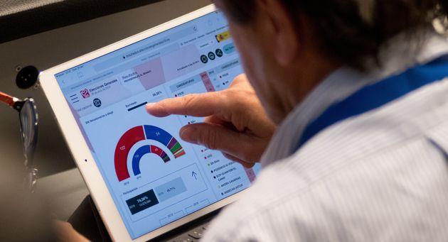 Un journaliste consulte la répartition des votes aux législatives espagnoles, dimanche...