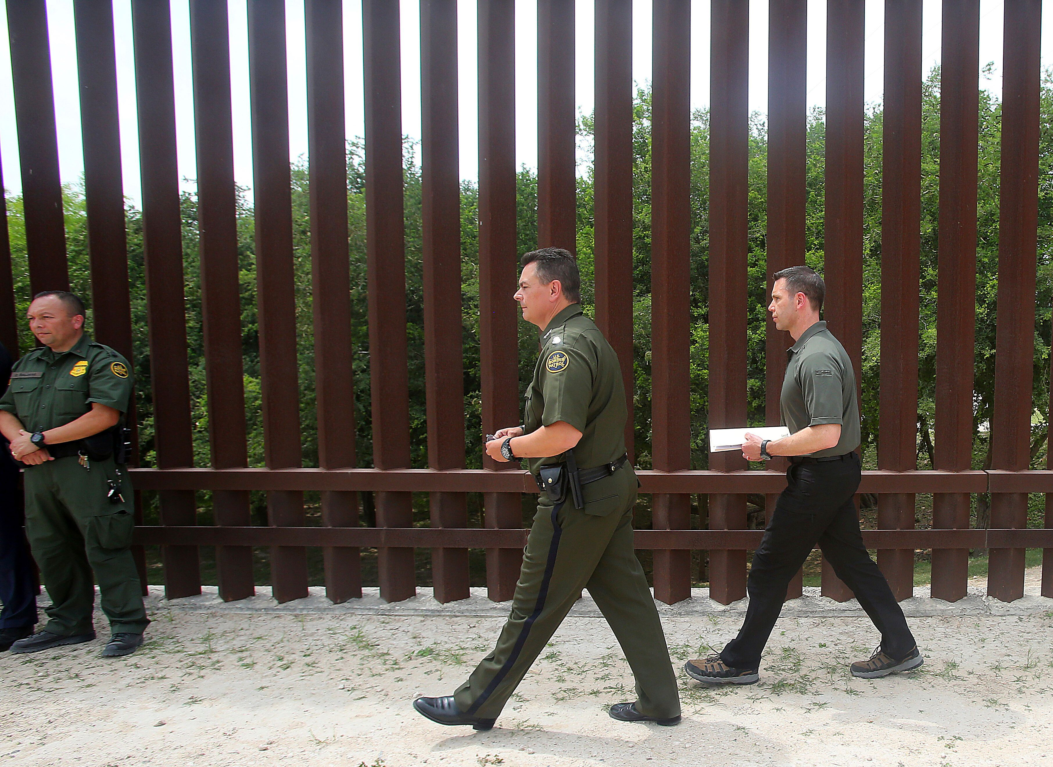Acting Homeland Security Secretary Kevin McAleenan, right, walks along a portion of the border wall with Rio Grande Valley Border Patrol Sector Chief Rodolfo Karisch to meet with the media, Wednesday, April 17, 2019, in Hidalgo, Texas. (Joel Martinez/The Monitor via AP)
