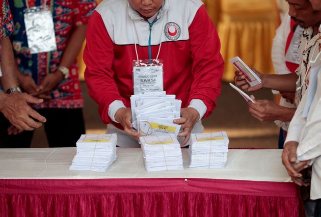 Electoral workers count ballots during the election at a polling station in Jakarta, Indonesia, on April...