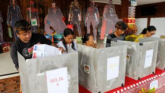 People cast their ballots in front of movie Avengers characters cutoutsvat a polling station during election in Bali, Indonesia on Wednesday, April 17, 2019. Voting is underway in Indonesia's presidential and legislative elections after a campaign that that pitted the moderate incumbent against an ultra-nationalist former general. (AP Photo/Firdia Lisnawati)