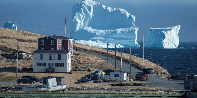Residents view the first iceberg of the season as it passes the South Shore, also known