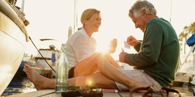 Couple sitting on marina pier playing cards, Redondo Beach, California,