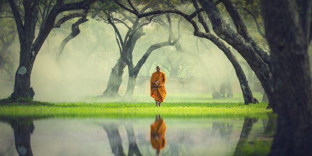 Monk hike in deep forest reflection with lake, Buddha Religion