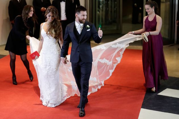 Newlywed Lionel Messi flashes a thumbs up as he and his bride Antonella Roccuzzo come out on to a red...