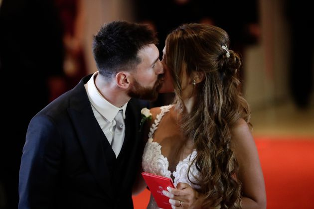 Newlyweds Lionel Messi and Antonella Roccuzzo kiss while posing for photographers on the red carpet after...