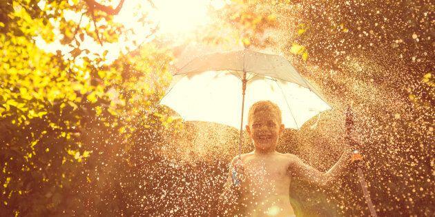 Boy splashing with water in garden on summer day, holding