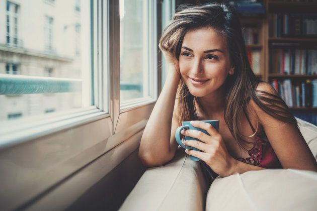Beautiful young woman holding a cup of coffee looking through a house window. Shot made during Istockalypse...