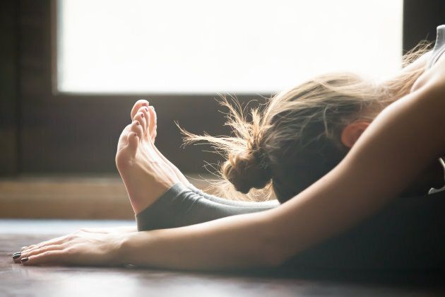 Young woman practicing yoga, sitting in Seated forward bend exercise, paschimottanasana pose, working...