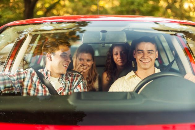Four young people sitting in a car, going on vacation. Two males and two females, all Caucasian in their