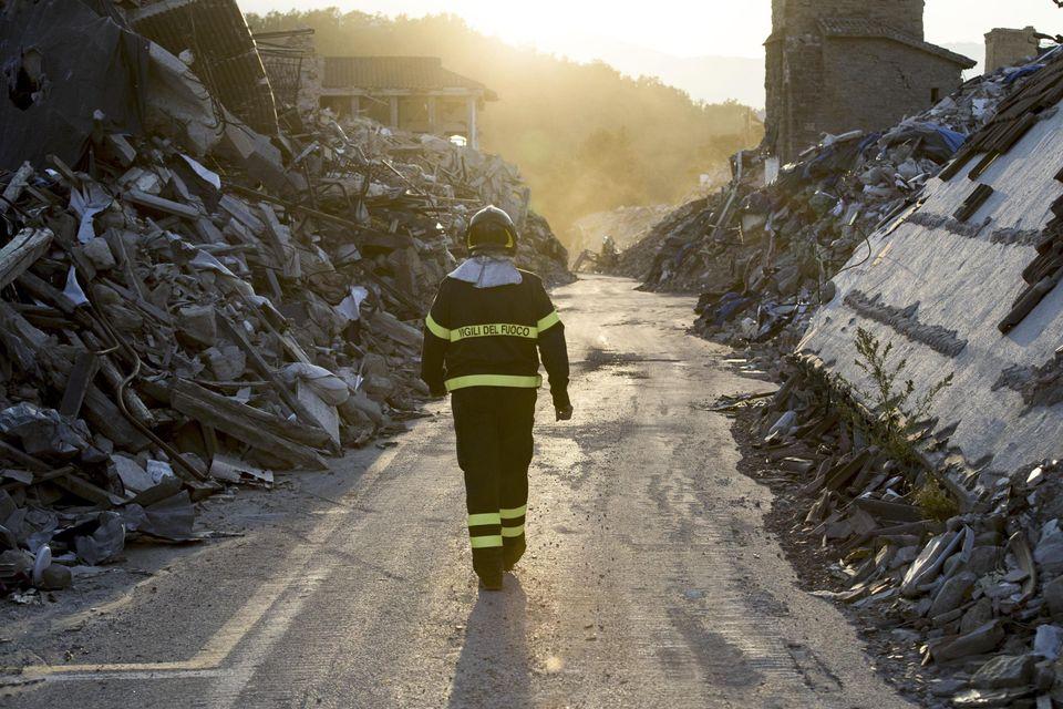 Un vigile del fuoco cammina su Corso Umberto I. Amatrice, 1 agosto 2017ANSA/MASSIMO