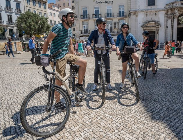 LISBON, PORTUGAL - AUGUST 10: Tourists ride B-Twin electric bicycles near Praca Dom Pedro IV on August...