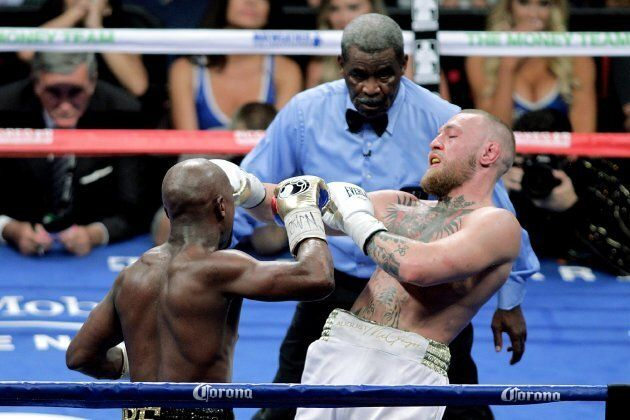 Referee Robert Byrd (C) watches as boxer Floyd Mayweather Jr. (L) and mixed martial arts star Conor McGregor...