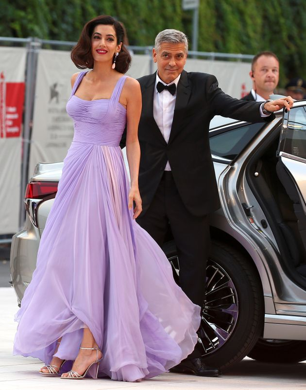 Actor and director George Clooney and his wife Amal arrive during a red carpet event for the movie