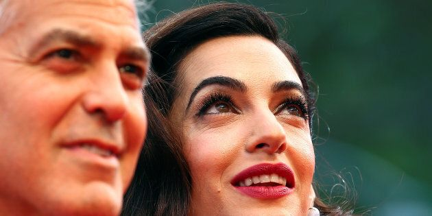 Actor and director George Clooney and his wife Amal pose during a red carpet event for the