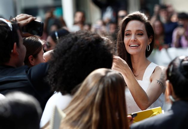 Executive producer Angelina Jolie signs autographs as she arrives on the red carpet for the film