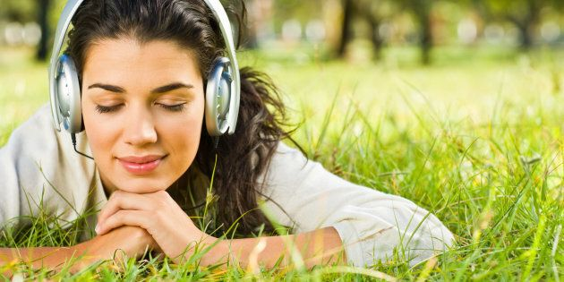 Smiling young woman listening to music at